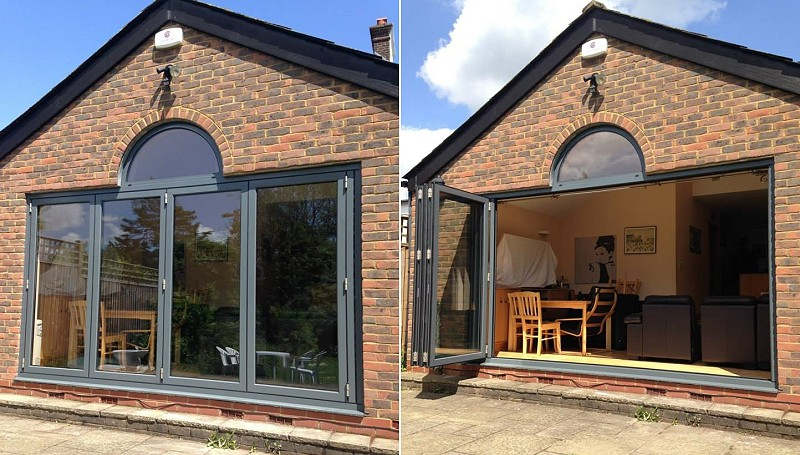 Tring, Herts: 4-panel bifold door in anthracite aluminium with demi-lune toplight.
